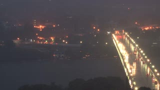 Bright Bridge Traffic in Dark Storm