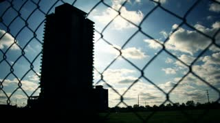 Building Shilouette Fence Afternoon Time Lapse. Time lapse silhouette of a building through a chain-link fence on a late afternoon during sunrise. Rendered in UltraHD 4K from high resolution stills.