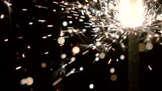 Burning sparkler against black background. Super slow motion shallow focus video