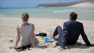Business couple sitting on the beach and relaxing