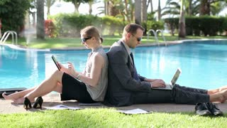Business couple working together by the poolside
