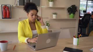 Business female talking with customer on the mobile phone. African mixed race head of department speak with colleagues on the cell and discussing report. Attractive black boss talk with employee on