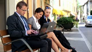Business people meeting and using technology on the bench in the city