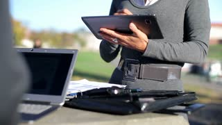Business people with laptop, tablet computer and documents, outdoors
