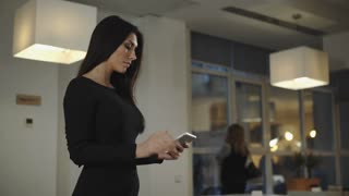 Business woman standing in the office and talking with a tablet. UHD