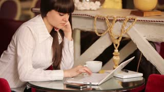 Businesslady thinking about something and typing on laptop