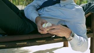 Businessman eating orange on sunbed, steadycam shot