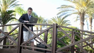 Businessman finish work with laptop on his vacation in tropical garden