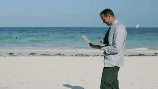 Businessman finish working on laptop on the beach