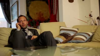 Businessman gets coffee from wife during a telephone call in livingroom