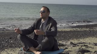 Businessman meditating on a sunny beach in the morning, slow motion shot
