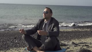 Businessman meditating on a sunny beach in the morning, slow motion