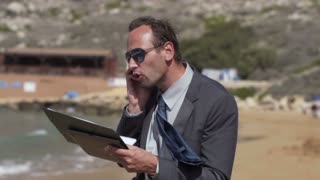 Businessman screeming to the cellphone on the beach, slow motion shot at 240fps