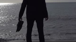 Businessman silhouette standing on a sunny beach in the morning, slow motion