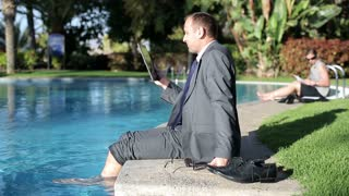 Businessman sitting by the poolside and chatting on tablet computer