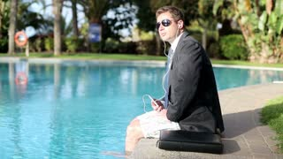 Businessman sitting by the swimming pool and listening music
