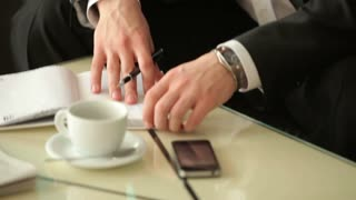 Businessman sitting in a cafe and looking seriously at camera