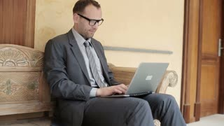 Businessman sitting on bench in antique hotel using laptop computer, steady