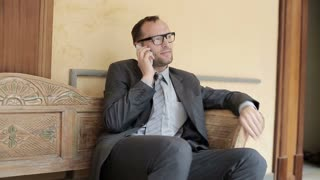 Businessman sitting on bench in antique hotel using mobilephone, steady