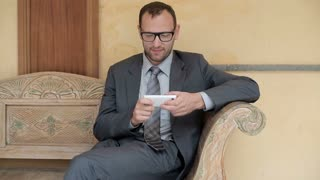 Businessman sitting on bench in luxury hotel using mobilephone, steady