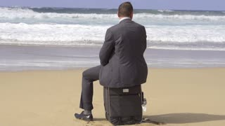 Businessman sitting on suitcase on the beach, slow motion shot at 240fps