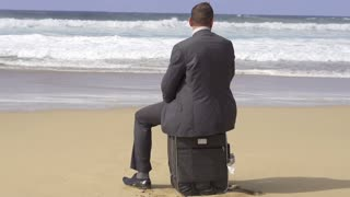 Businessman sitting on suitcase on the beach, slow motion shot at 60fps