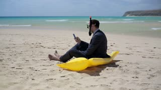 Businessman sitting on the beach on inflatable mattress and texting message
