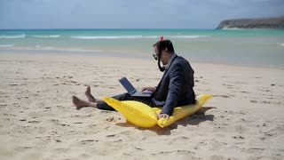 Businessman sitting on the beach on inflatable mattress and working on laptop