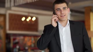 Businessman speaking by phone and smiling