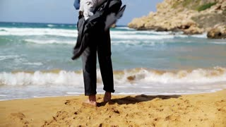 Businessman standing on the beach without shoes