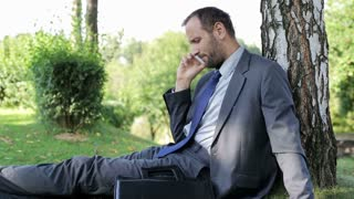 businessman talking on the cellphone nd sitting on the grass