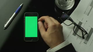 Businessman Using Mobile Phone with Green Screen which Lying on the Table. Top view.