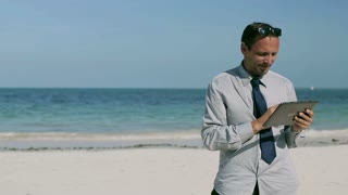 Businessman using tablet and smiling to the camera on the beach