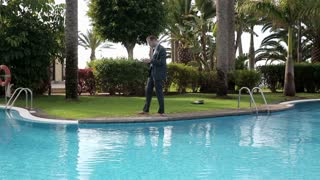 Businessman walking by the poolside with cellphone