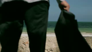Businessman walking on the beach, steadycam shot
