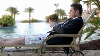 Businessman with cellphone on his vacation lying on sunbed by swimming pool