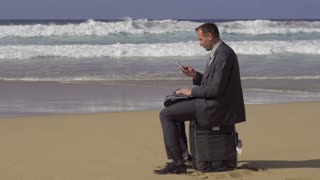 Businessman with cellphone sitting on suitcase on the beach, slow motion 240fps