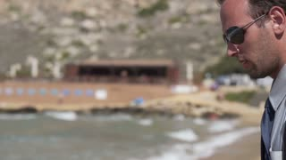 Businessman with cellphone standing on the beach, slow motion shot at 120fps