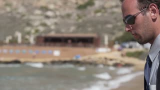 Businessman with cellphone standing on the beach, slow motion shot at 240fps