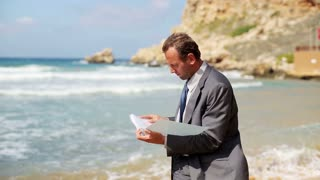 Businessman with documents standing on the beach