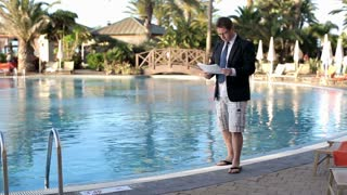 Businessman with documents walking by swimming pool on his vacation