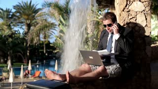 Businessman working by the waterfall on his vacation