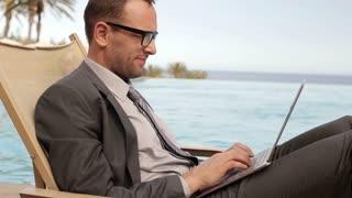Businessman working on laptop in tourist resort, steadicam shot