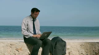 Businessman working on laptop on the beach