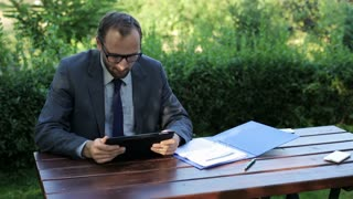 businessman working on tablet in the garden