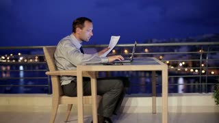 Businessman working on the terrace in the evening and getting bad news