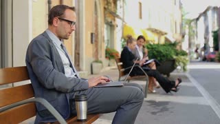 Businessman working sited on a bench and getting bad news by email