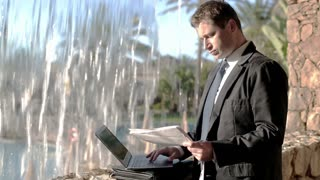 Businessman working with laptop computer by the waterfall on his vacation