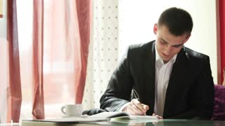 Businessman writing something and looking at camera