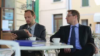 Businessmen sitting in the restaurant outside with tablet computer